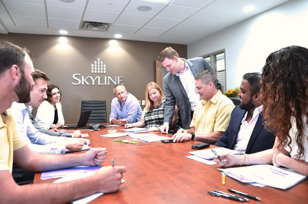 Skyline Energy President Rob Stein in a boardroom with Skyline Energy staff
