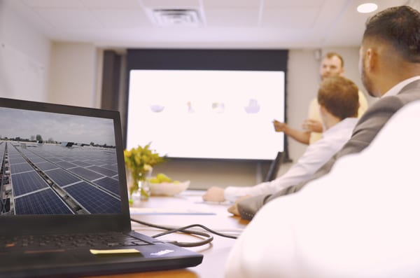 Laptop on boardroom table with image of Skyline Energy solar energy assets